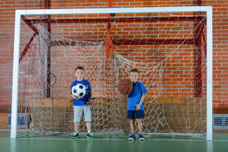 together standing: Two young schoolboys playing ball together standing in the goals on an indoor court, one with a basketball, one a soccer ball