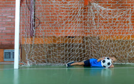 indoor soccer: Young goalie saving a goal on an indoor soccer court lying across the goals on his side clutching the ball