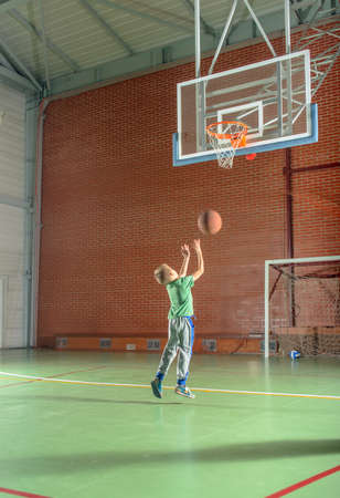 Young boy shooting for goal in basketball tossing the ball for the hoop as he practices on an indoor court Standard-Bild