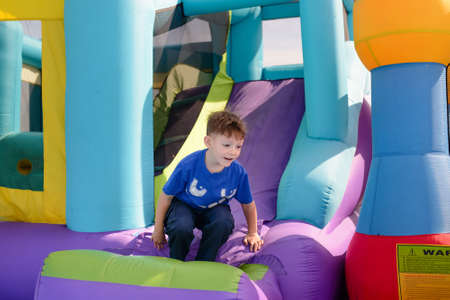 outspread: Carefree young boy playing on a bouncy castle exiting a colorful purple slide with his arms outspread and a happy smile