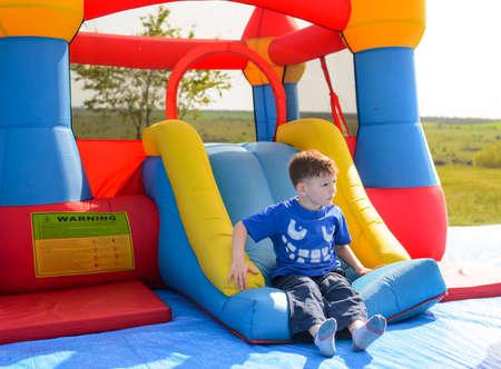 Het jonge jongen spelen op een kleurrijke springkussen op een kermis of een pretpark op een zonnige zomerdag