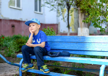dissapointed: Bored little boy sitting waiting with his head resting on his hands and a sulky expression on a rustic blue bench outdoors