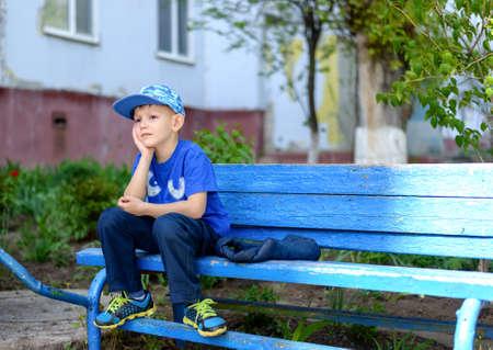 psicologia infantil: niño aburrido que se sienta esperando con la cabeza apoyada en las manos y una expresión malhumorada en un banco azul al aire libre rústico Foto de archivo