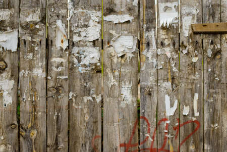 tearing down: Rough worn out old wooden plank fence background with torn off posters and red spray paint graffiti and rusty nails Stock Photo