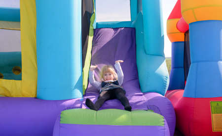 fairground: Cute little fair haired girl playing on a colorful bouncy castle at a fairground waving and smiling as she exits the slide