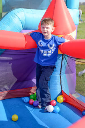 fairground: Handsome little boy standing on a bouncy castle surrounded by balls in spring sunshine at a fairground or amusement park