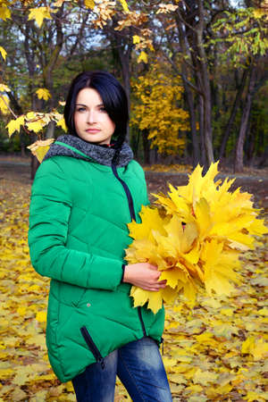 anorak: Single serious woman in green coat looking down at bundle of maple leaves in her hands at park surrounded by trees