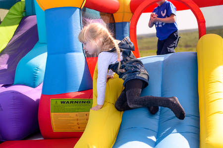Pretty little blond girl playing on a slide on an inflatable bouncy castle at a fairground, side view