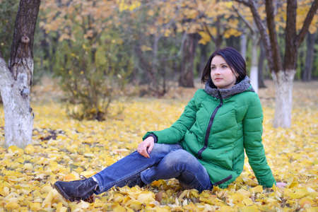 laying on back: Daydreaming single woman in green winter coat laying back on ground among yellow leaves spread out around her under trees in scenic park
