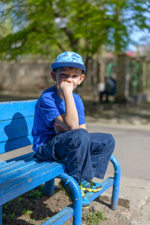 dissapointed: Patient young boy sitting waiting on a blue wooden outdoor bench in a trendy blue outfit with his hand to his chin and a bored expression