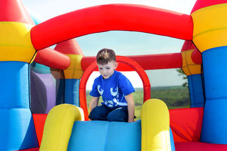 outspread: Young boy playing on a colorful bouncy castle at a fairground or amusement park on a sunny summer day Stock Photo