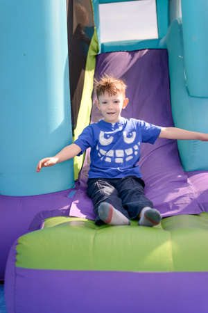 exiting: Carefree young boy playing on a bouncy castle exiting a colorful purple slide with his arms outspread and a happy smile