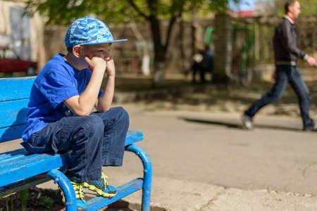 psicologia infantil: joven paciente sentado esperando en un banco al aire libre de madera de color azul con un traje azul de moda con la mano a la barbilla y una expresión de aburrimiento