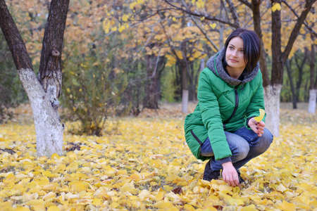 anorak: Daydreaming single woman in green winter coat laying back on ground among yellow leaves spread out around her under trees in scenic park