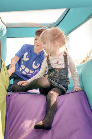 get ready: Cute young brother and sister having fun as they get ready to go down inflatable purple and green outdoor slide