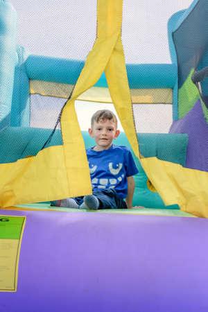 brincolin: Un solo niño pequeño lindo cuus con la cara sudorosa mirando desde la entrada de la casa hinchable Foto de archivo