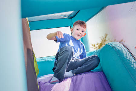 going down: Single little happy boy dressed in blue with socks going down inflatable purple and green outdoor slide Stock Photo
