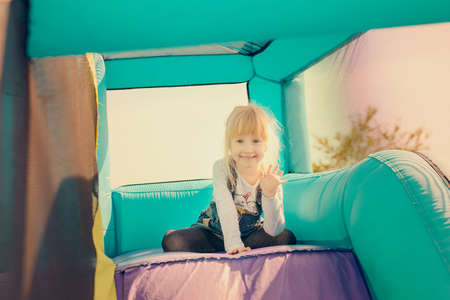 jeans skirt: Single little happy blond girl dressed in blue jeans skirt getting ready to go down inflatable purple and green outdoor slide