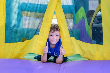 brincolin: Single cute little curious boy with sweaty face looking from entrance of bouncy house