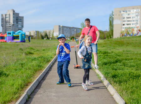 clowning: Happy little boy and girl clowning around outdoors laughing and pulling faces as they run along a path through an urban path Stock Photo