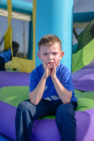 Exhausted boy with sweaty face and hands near mouth in blue short sleeve shirt sitting near bouncy house entrance