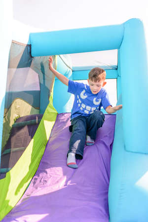 inflatable: Cute little boy sliding down blue and purple inflatable outdoor carnival amusement ride