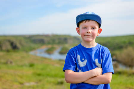 Happy attractive confident young boy in a trendy blue outfit standing with folded arms grinning at the camera, countryside view with copy space Standard-Bild