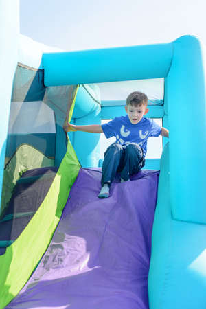 outspread: Cute little boy sliding down blue and purple inflatable outdoor carnival amusement ride