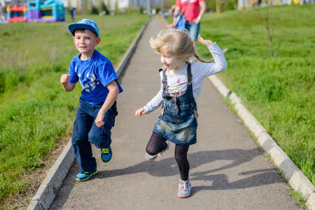 Happy little boy and girl clowning around outdoors laughing and pulling faces as they run along a path through an urban path Stock Photo