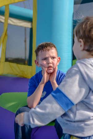 brincolin: Sudada niño enfrentado en camisa azul de manga corta que se sienta con un amigo cerca de entrada de la casa hinchable