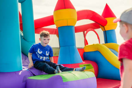 Two little boys in short sleeve shirts playing on inflatable slide and castle outdoors Standard-Bild