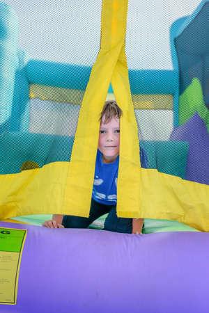 brincolin: linda poco de curiosidad solo muchacho con la cara sudorosa mirando desde la entrada de la casa hinchable