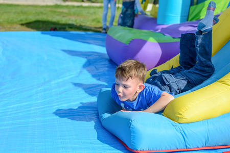 outspread: Handsome little boy lies on a bouncy castle surrounded by balls in spring sunshine at a fairground or amusement park