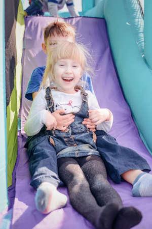 Schattige jonge broer en zus naar beneden outdoor opblaasbare bouncy dia in paars en blauw