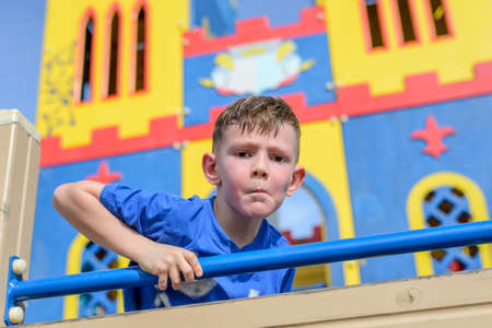 peering: Single cute sweating male child framed by climbing ropes peering from colorful playground house outdoors