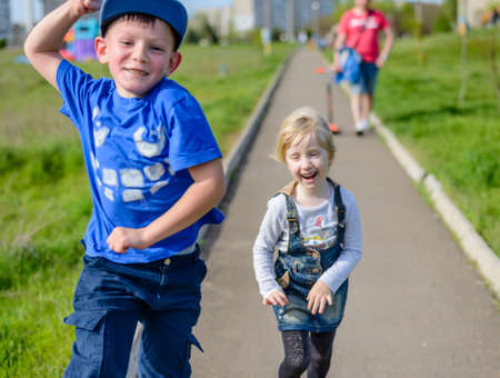 pulling faces: Happy little boy and girl clowning around outdoors laughing and pulling faces as they run along a path through an urban path Stock Photo