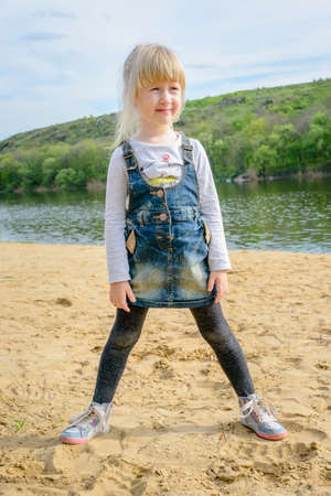 denim skirt: Cute little blond girl standing on a sandy beach in a denim skirt and leggings smiling happily as she looks to the side Stock Photo