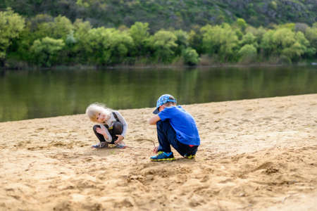 girl squatting: Little boy in hat and blond girl playing on sand near river edge with short tree lined hill in background with copy space