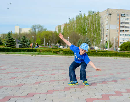 agile: Agile young boy in a trendy blue outfit doing cartwheels in a paved urban square balancing on his hands