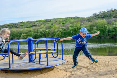 alongside: Boy running alongside a merry-go-round as he spins a little girl around at speed on an outdoor sandy playground alongside a lake Stock Photo