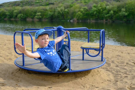 supple: Little boy on a spinning merry-go-round waving at the camera as he looks back over his shoulder outdoors on a sandy beach near a watercourse