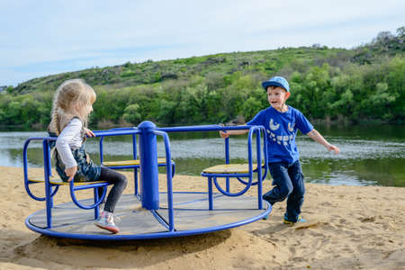 glee: Little boy pushing a small blond girl on a merry-go-round on a sandy beach alongside a lake or river laughing with glee Stock Photo