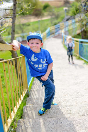 fatigued: Young boy in a trendy blue outfit pausing for a rest on steep flight of outdoor stairs on a rural hillside leaning on the rail and grinning up at the camera