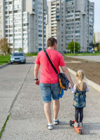 urban parenting: Father pulling his small daughter along on a scooter as they walk along an urban road towards apartment blocks, rear view