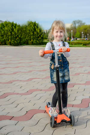 footplate: Smiling little blond girl posing on a toy scooter resting her arms and chin on the handlebars, front view on a paved outdoor square