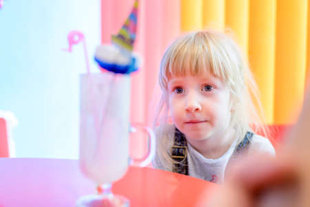 eyeing: Cute pretty little blond girl eyeing a milkshake glass with a decorative umbrella which she has just finished with a look of satisfaction