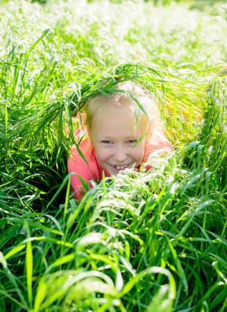 spontaneous expression: Cute happy little girl blond playing in long lush green spring grass peering out at the camera with a cheeky smile