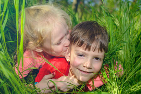 spontaneous expression: Fun loving little boy and girl lying on their stomachs in fresh long green spring grass grinning playfully at the camera as they enjoy their vacation Stock Photo