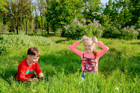 crouch: Two happy young children, a blond girl and boy, playing in lush green long grass in a garden park grinning happily at the camera as they crouch down