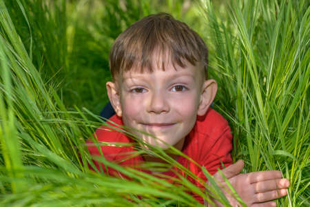 jaunty: Smiling handsome little boy lying on his stomach peering out from lush green spring grass at the camera